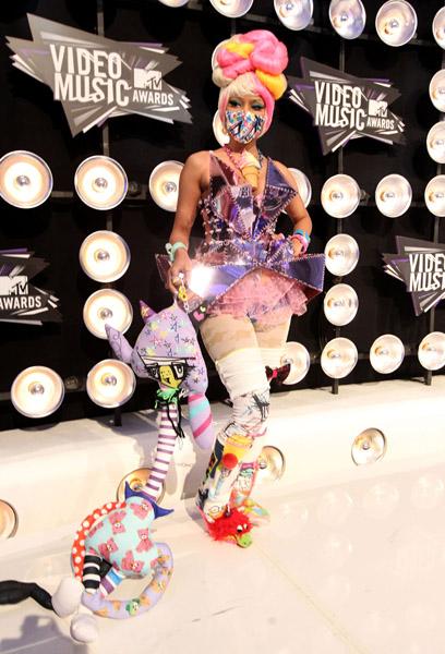 """Durante el 2011 VMAs, Nicki llevaba un vestido inspirado en Harajuku con fragmentos de espejo (un símbolo que representa la  fragmentación monarca de la personalidad). La combinación de accesorios """"para niños"""" con la sensualidad del corte del vestido (que es """"revelacdora"""" en los lugares correctos) es un poco cuestionable."""